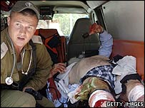 An Israeli soldier treats a man wounded in an attack on the Israeli settlement of Neve Dekalim