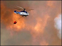 Firefighting helicopter flying, surrounded by flames