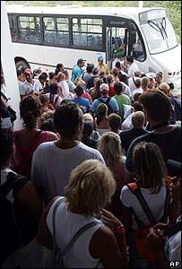 Turistas esperan fuera de su hotel para ser trasladados a refugios en Cancún, México
