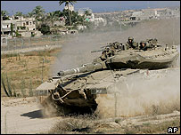 Israeli tank drives close to a Palestinian town in Gaza