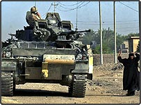 A British tank passes an Iraqi woman in the Basra, Iraq