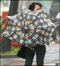 A woman struggles with her umbrella against powerful gusts of wind and torrential rains brought by typhoon Haitang, 18 July, Taipei