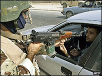 An Iraqi soldier points his rifle at a driver at a checkpoint
