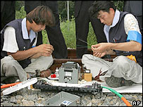 Two South Korean workers of Korea Telecom work near Paju, north of Seoul, Monday, July 18, 2005.