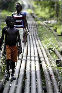 Children walk along an oil pipeline in Warri, Nigeria
