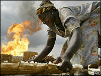A woman dries her tapioca, next to a gas a flare near an oil flow station in Warri, Nigeria