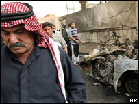 Men inspect the wreckage of a car in Doura