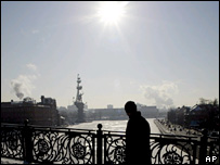 A man walking across a bridge over the Moskva river