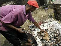 People slaughter chickens to be sold at a market in Nigeria