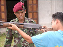 Officer teaching Buddhist villager how to fire a rifle