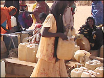 Sudanese women queue for water in refugee camp in Chad