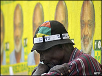 A man sits in front of posters of Rene Preval in Port-au-Prince, Haiti