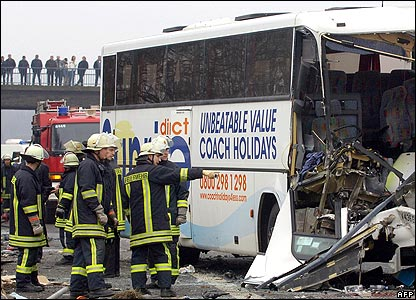 Fire crews study one of the damaged coaches at the scene