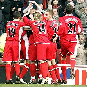Fabio Rochemback is mobbed by his team-mates