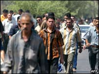 People leave the scene of the suicide bombing at a Baghdad army recruitment centre 