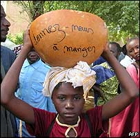"Girl protester carrying an empty bowl with ""give us something to eat"" written on it"