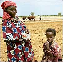 Una mujer junto a su hija en un campo afectado por la sequía