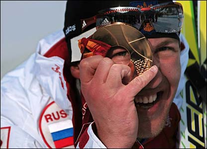 Russia's Eugeni Dementiev peers through his gold medal