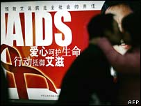 A couple in front of an Aids awareness poster in Beijing