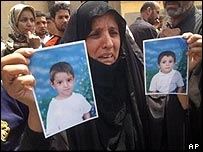 An Iraqi mother holding photos of her slain children