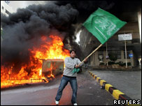 Youth waving Islamic flag as fire burns in Beirut