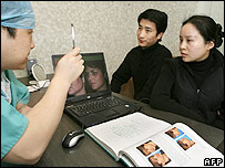 Fang Liang (L) and Tang Xiaoyan (R) discuss plastic surgery options with a surgeon at the ConBio Plastic Surgery Hospital in Shanghai 13 February 2006.