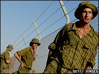 Israeli soldiers stand watch at a fence near Gaza