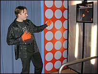 Hombre frente a pantalla haciendo mímica de guitarra.