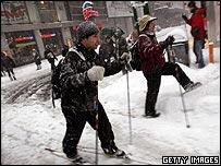 Unos neoyorquinos con esquís tras la nevada.