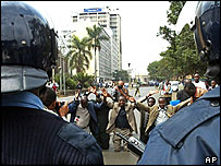 Kenyan activists kneel down on the road as riot police stop them in Nairobi