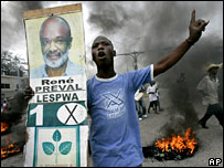 A Preval supporter by a burning roadblock in Haiti's capital, Port-au-Prince