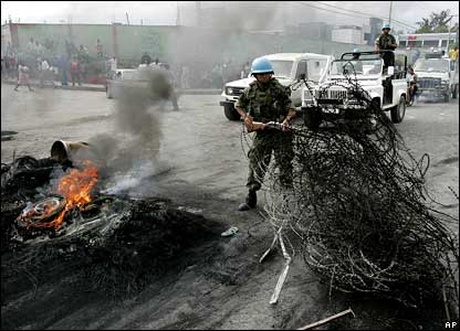 UN peacekeepers clear a barbed wire roadblock in Port-au-Prince