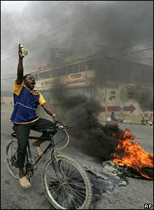 A Preval supporter cycles past a roadblock in Port-au-Prince