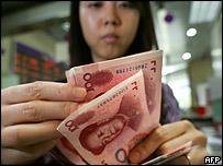 Empleada de un banco cuenta billetes de yuan