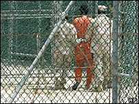Two guards walk with an inmate at the Guantanamo Bay detention camp in Cuba