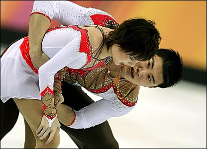 Zhang Hao helps his partner Zhang Dan (foreground) after she fell during their free programme