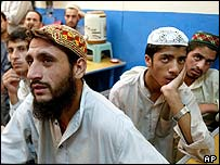 Religious students listen to President Musharraf defending raids on madrassas