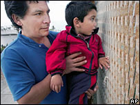 A Mexican and his grandson look through the US-Mexico border fence in Tijuana