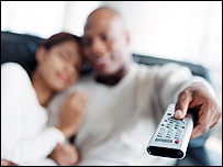 Couple with TV remote control