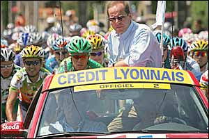Deputy Tour de France director Christian Prudhomme rides in front of the pack