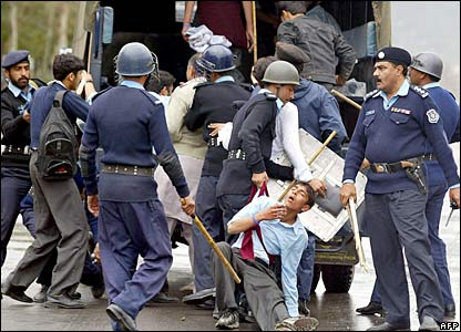 Pakistani policemen arrest students during a demonstration in Islamabad, 14 February
