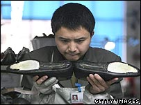 Worker in a shoe factory examines his products