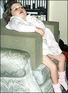 Photo of 4 year-old Jenny looking uncomfortable sitting in a makeshift chair