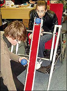 Photo of someone rolling a ball down a boccia ramp using their chin