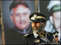 Traffic policeman keeps an eye on protests in front of portrait of Pres Musharraf