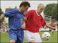 AFC Wimbledon's Shane Smeltz takes on FC United's Rob Nugent
