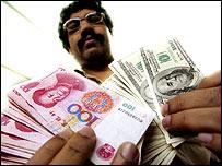 Cambista con billetes de yuan y dólar