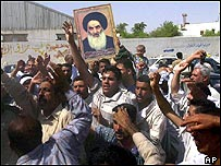 Shiite faithful hoist a picture of Grand Ayatollah Ali Husseini Al-Sistani