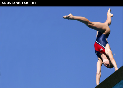 A diver begins a dive from the handstand position
