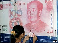 Young girl checks her yuan note against a bigger version in Beijing